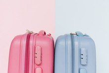 Two Blue And Pink Plastic Luggage Suitcases On Dual Background