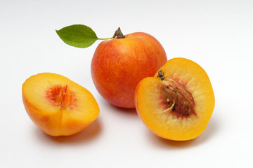 Ripe nectarine or apricot with a green leaf and cut fruit with a bone on a white background, close-up, natural color.