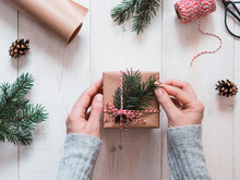 Christmas Gift Wrapping Background.Female Hands Holding Christmas Present Box Wrapped In Kraft, Top View. Winter Holidays Concept, Flat Lay.Woman With Pink Pastel Matte Manicure Packing Christmas Gift