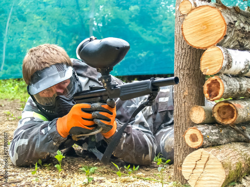 Photo  A paintball player who is ready to shoot from hiding