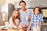 Vater und Kinder beim Frühstück in der Küche