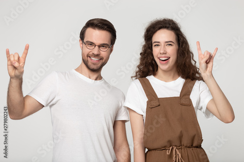Valokuva  Millennial couple showing rock and roll hand gesture studio shot