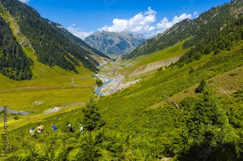 Fotografie, Obraz  Sonamarg, Kashmir - August 12 2017: A group of trekkers make their way up a mountain in Sonamarg, Jammu & kashmir amidst beautiful green pastures, valley, meadow and flowers