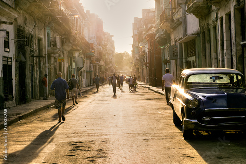 fototapeta na ścianę Cuban people in the street of Old Havana going to work with the first lights of the morning, Havana, Cuba