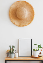 Modern Minimalist Light Interior In Details. Straw Hat On The Wall Over The Small Wooden Console