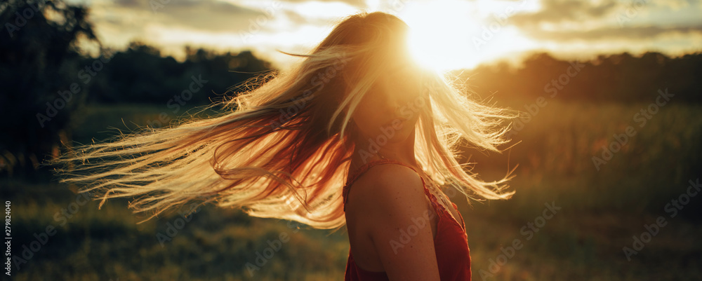 Fototapety, obrazy: Young blond woman stands on meadow with loose hair lit by sun.