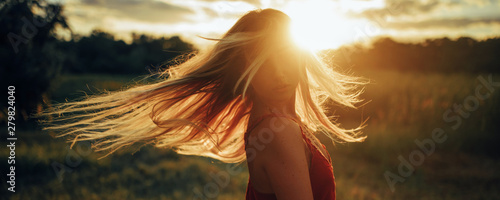 Fotografija Young blond woman stands on meadow with loose hair lit by sun.