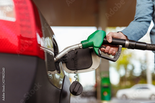 Fototapeta  Crop hand refueling car on station