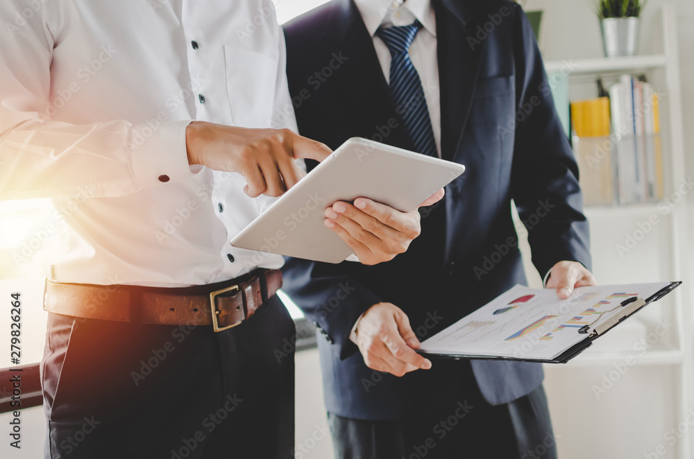 Fototapeta Job training. new manager boss mentor standing teaching online work with mobile tablet to young intern apprentice learning statistics chart, working at office, internship, practicum, trainee concept