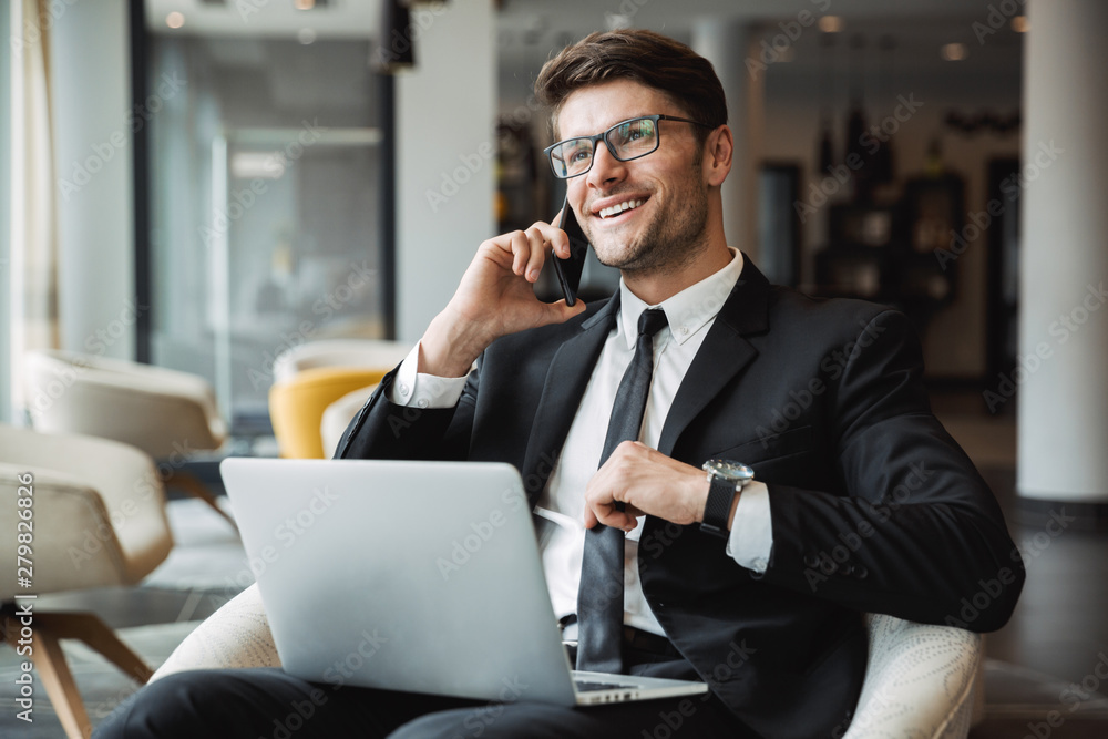 Fototapeta Portrait of happy young businessman using laptop computer and talking on smartphone in hotel hall