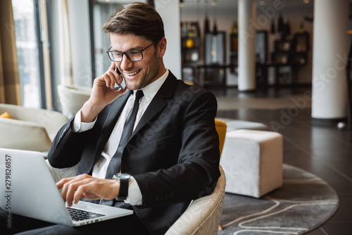 Photo of happy young businessman using laptop computer and talking on smartphone in hotel hall