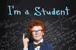 Smart student boy pointing finger on chalkboard background with I'm student text. Back to school concept