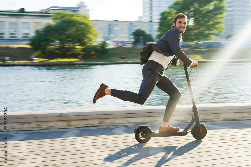 Fototapety, obrazy: Young business man in a suit riding an electric scooter on a business meeting.