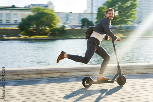 Young business man in a suit riding an electric scooter on a business meeting.
