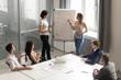 Leinwandbild Motiv Asian and caucasian female speakers give flip chart office presentation