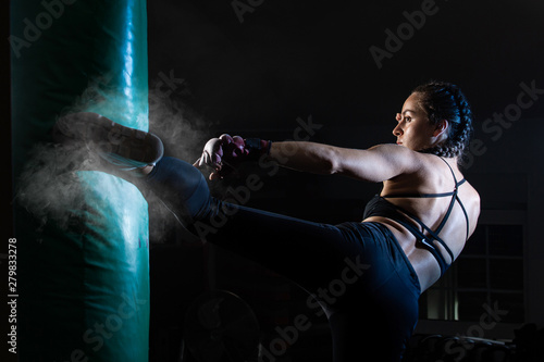 Young female boxer punching a bag on a sports training in a gym. Fototapet