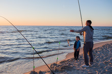 Father And Son Fishing On The Beach Of   Baltic Sea In The Sunset Time.