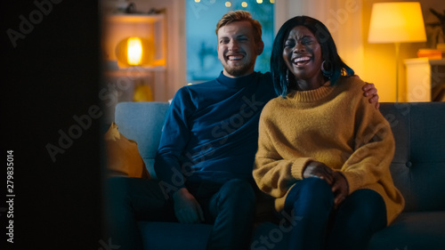 Fotografie, Obraz Happy Diverse Young Couple Watching Comedy on TV while Sitting on a Couch, they Laugh and Enjoy Show