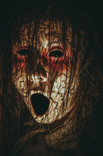 Creepy Girl With Black Eyes Opened Mouth And Cracked Skin Close-up Portrait