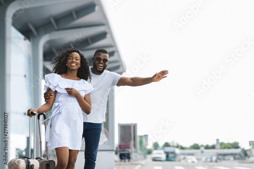Young african couple standing near airport trying to stop car - 279841027