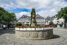 The Petrus Fountain In Brilon Is Decorated With Geraniums. The Half Timbered Houses On The Marketplace Have Set Up Flags. Friedrich Road With Pennants.