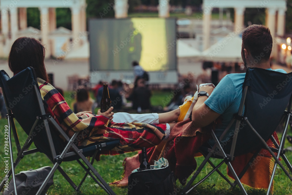 Fototapeta couple sitting in camp-chairs in city park looking movie outdoors at open air cinema