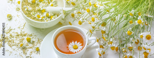 Staande foto Thee Rural still-life - cup of brewed chamomile tea on the background of a bouquet of daisies, closeup
