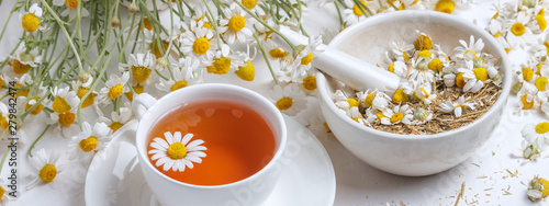 Photo Rural still-life - cup of brewed chamomile tea on the background of a bouquet of