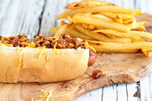 Hot Dog With Chilli, Cheddar Cheese And Mustard. Selective Focus With Blurred French Fries In The Background.