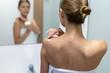 Woman applying body cream on shoulder in bathroom