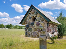 Closeup Of Stone Birdhouse In Rural Field With Summer Sky