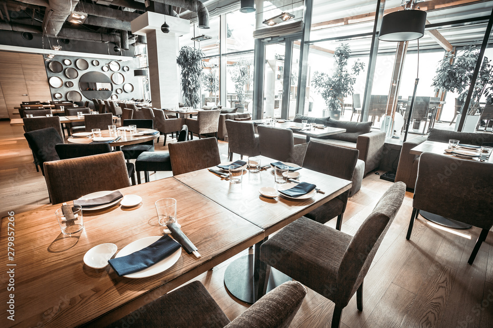 Fototapety, obrazy: Spectacular interior of the contemporary restaurant in stylish grey shades. The main hall with the wooden tables, chairs and velvet sofas. Glass wall with entrance to the terrace.