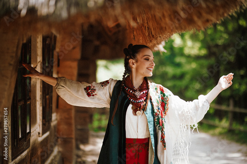 Stampa su Tela  Beautiful girl in a traditional Ukrainian dress dances and smiles