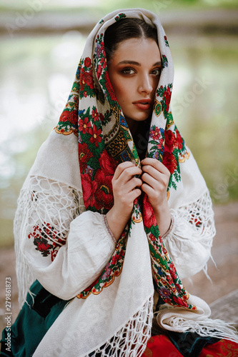 Carta da parati Beautiful girl in a traditional ethnic dress with an embroidered cape on her hea