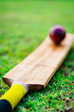 Red Cricket Ball With Bat In G...