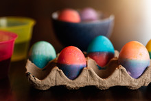 Close Up Of Dyed Easter Eggs In A Carton And In A Bowl On A Table.