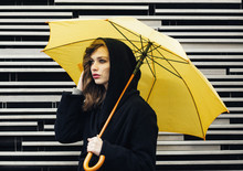 Young Woman In Black Coat Holding Yellow Umbrella