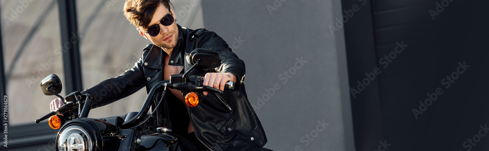 Fototapeta panoramic shot of motorcyclist in leather jacket sitting on motorcycle and looking away