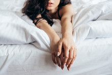 Selective Focus Of Sensual Brunette Young Woman Lying On Bed