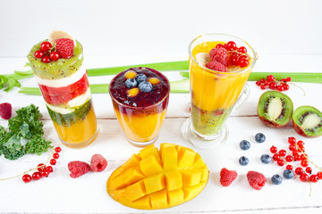 Multi-layered, colorful smoothie in glasses, spilled fruits around