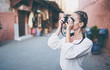 Leinwandbild Motiv Tourism and technology. Happy young woman taking photo of  Marrakesh old town. Traveling by Morocco.