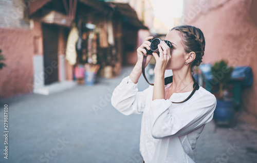 Foto auf Leinwand Marokko Tourism and technology. Happy young woman taking photo of Marrakesh old town. Traveling by Morocco.
