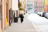 Fototapeta Fototapeta Londyn - Stara kobieta w czarnym stroju, pochylona idzie chodnikiem przez miasto.