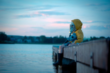 The Child In The Gas Mask Is Sitting On The Platform At The Lake. Environment Pollution.