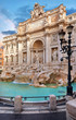 Trevi Fountain in Rome, Italy. Ancient fountain. Roman statues at piazza in old medieval city among traditional italian houses and street lamps. Famous landmark. Touristic destination for vacation.