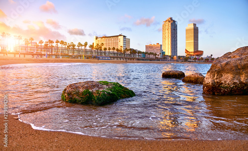 Foto auf Leinwand Barcelona Barcelona, Spain. Panoramic view at Barceloneta beach from sea. View with stones. Sunset landscape with blue sky. Sandy coastline with palms and waves of surf. Popular touristic vacation destination.