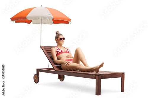 Fotografia Young beautiful woman in bikini on a sunbed with umbrella