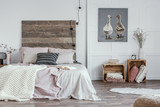 Spacious, feminine bedroom interior with rustic furniture, white walls, wooden crates and oil painting of animals. Real photo