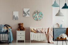 A Teddy Bear, Two Beds And A Large Clock On A Beige Wall In Bright And Warm Bedroom Interior For Twins. Real Photo