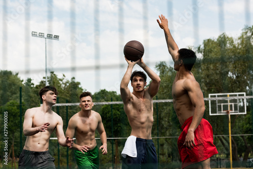 Fotoposter Eigen foto selective focus of shirtless sportsmen playing basketball at basketball court